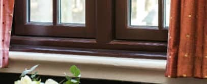 Close up of a gold modern handle on a brown Everest casement window