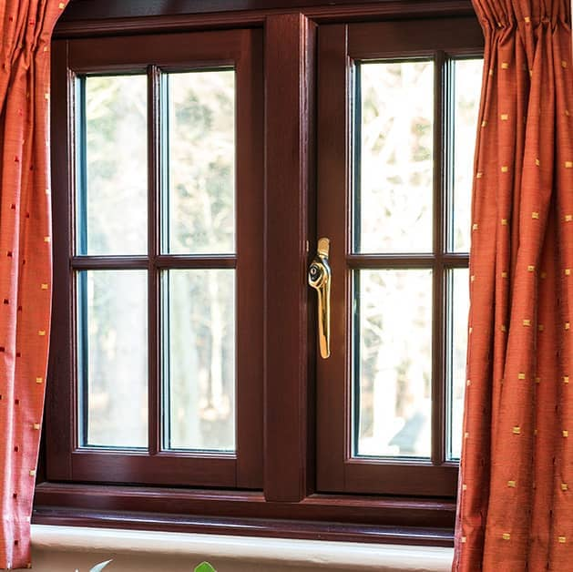 Brown Everest timber casement window with a gold modern handle