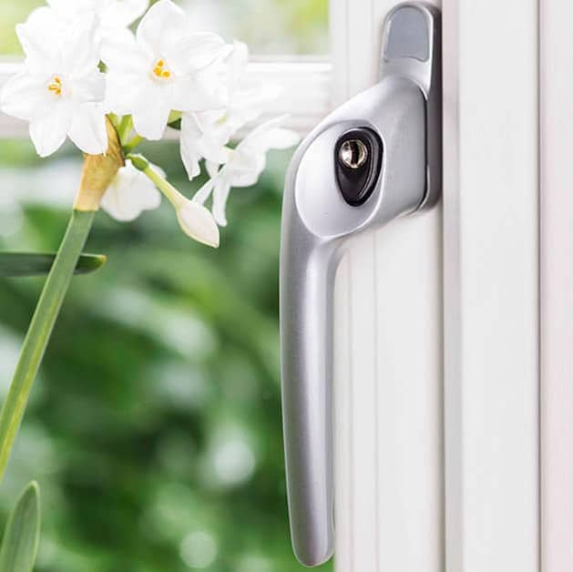An Everest chrome standard handle on white uPVC Everest window with flower
