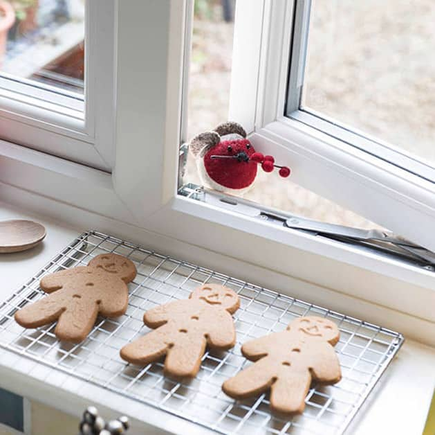 Kitchen white upvc window open slightly with christmas gingerbread men cooling