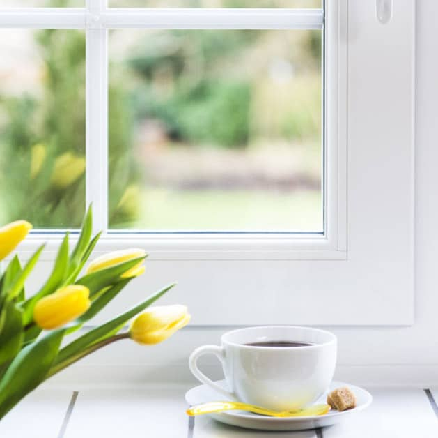 Close up of an Everest white tilt and turn window made from uPVC with a coffee in front of the window