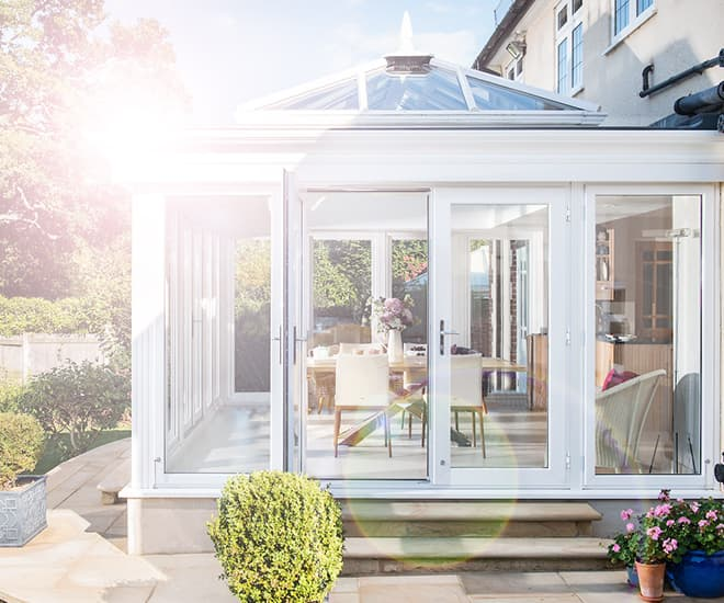 An Everest white uPVC conservatory with the sun shining