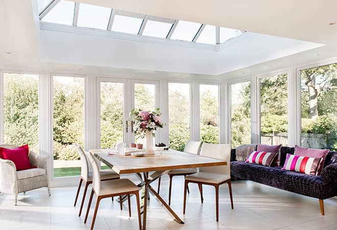 A large glass extension with white trim that has a dining table in the centre of the room and a glass conservatory roof letting in the sun.
