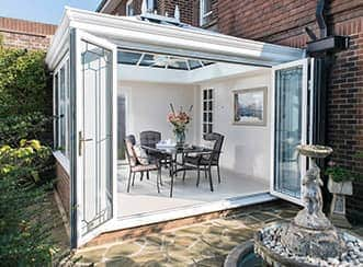 A classic conservatory in white uPVC with open doors displaying a dining table inside.