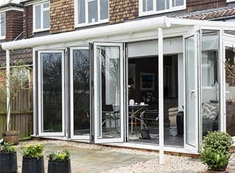 A large glass extension with white uPVC frames and tall glass conservatory doors opening out on to a garden.