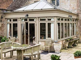 A stylish orangery in a light brown tan coloured uPVC that is well matched to the old brick house and shabby chic garden.