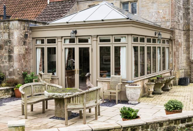 A timber orangery seamlessly blending into the exterior of a house