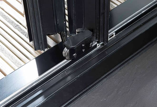 A close up of the folding mechanism of a black bifold door, looking out on to patio decking.