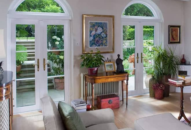 2 sets of white timber french doors in a living room giving a lovely view into the garden