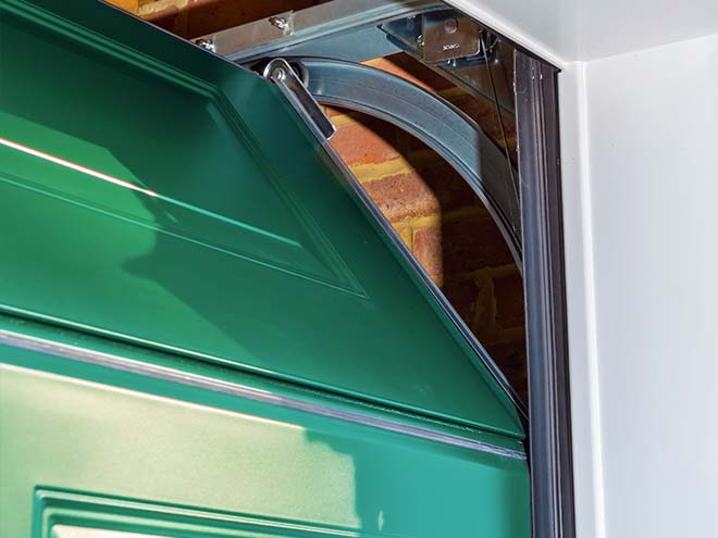 View of the opening of a sectional garage door from Everest, in a Racing Green