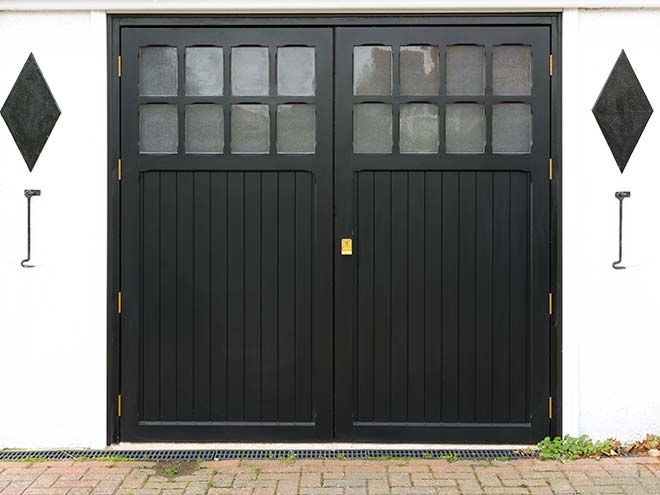 Full view of a blacck Side Hinged garage door from Everest