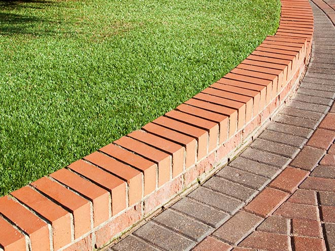 Close up view of the finish of Everest Artificial Grass meeting a brick curb