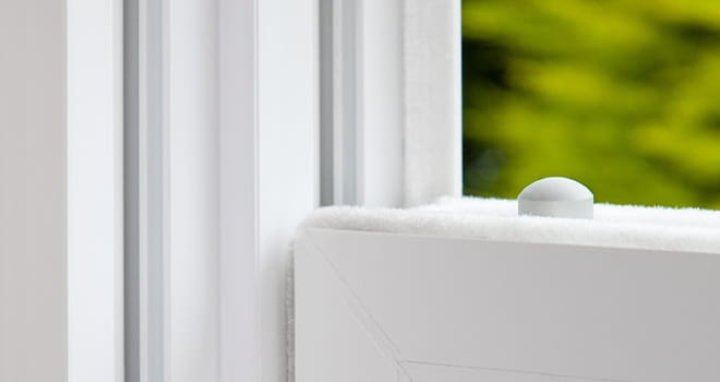 A close up fo a multi-point locking mechanism on a white Everest window